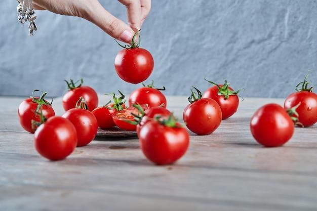 Hand met een tomaat met een bos tomaten op houten tafel