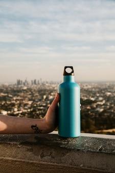 Hand met een turquoise roestvrijstalen fles met uitzicht op de stad