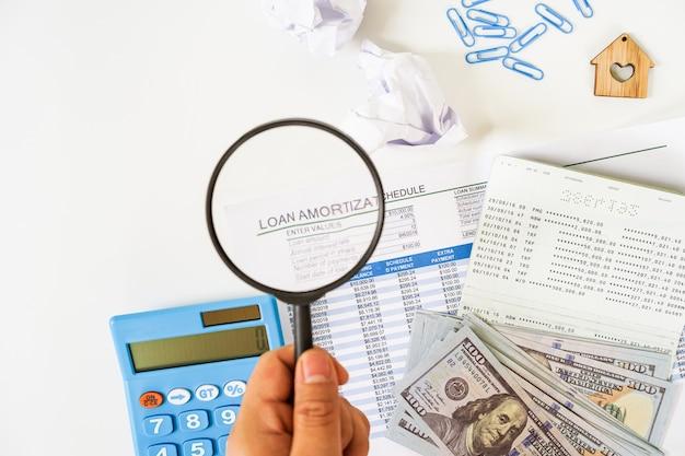Hand met een vergrootglas over lening schema blad, ons bankbiljet, rekenmachine, bankboekje plat lag op witte achtergrond.