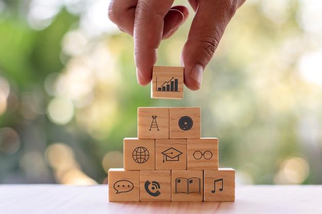 Hand met een vierkant houten blok met grafiekpictogram met financieel pictogramconcept van financiële en bedrijfsgroei.