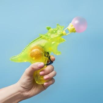 Hand met een waterpistool in de vorm van een neushoorn die een bel blaast