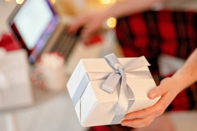 Hand met een witte doos met cadeau