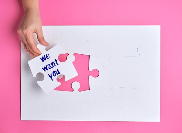 Hand met een witte puzzel met de woorden we willen jou