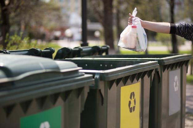 Hand met een zak met plastic afval over containers voor scheiding en sortering van glas