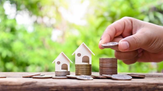 Hand met een zilveren munt en een replica van een huis op een stapel munten