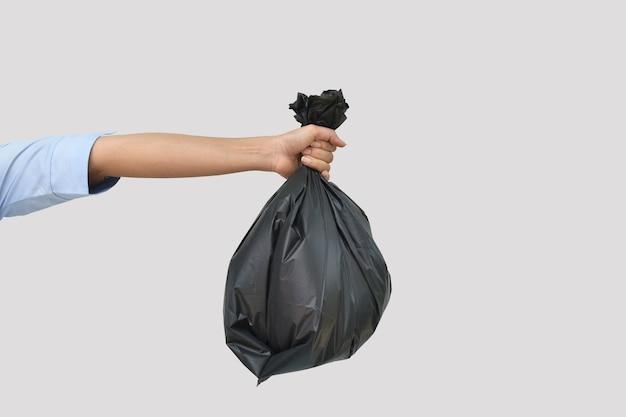 Hand met een zwarte vuilniszak op grijze achtergrond met uitknippad