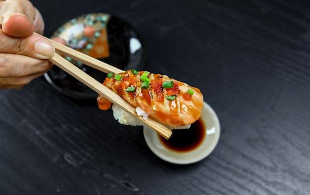 Hand met eetstokje voor het eten van japan eten