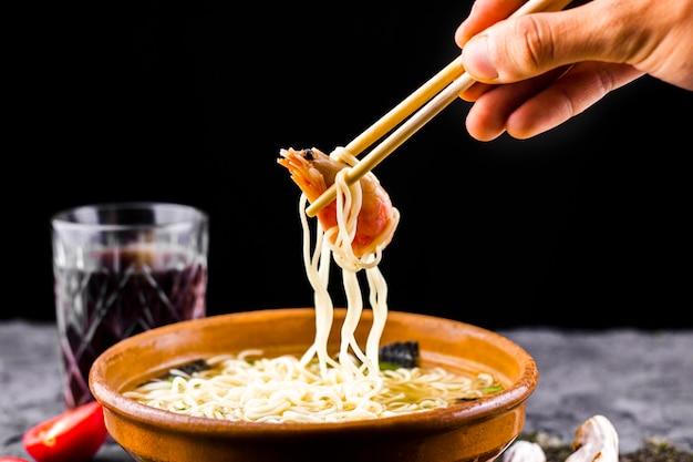 Hand met eetstokjes die garnalennoedels houden