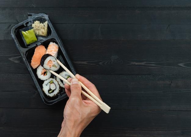 Hand met eetstokjes en sushibak. afhaalconcept.