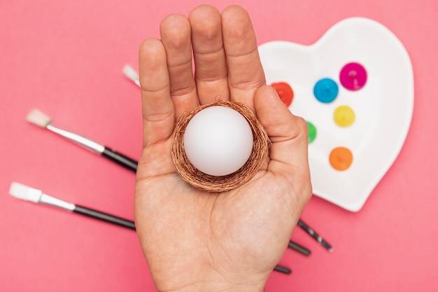 Hand met ei bereid om te worden geschilderd