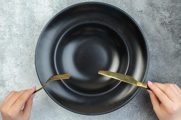 Hand met elegante vork en mes op zwart serviesgoed op een geïsoleerd grijs ijsoppervlak met vrije ruimte