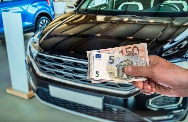 Hand met eurobankbiljetten, auto op achtergrond. financieel concept