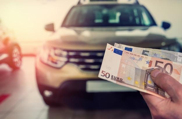 Hand met eurobankbiljetten, auto op de achtergrond. financieel concept