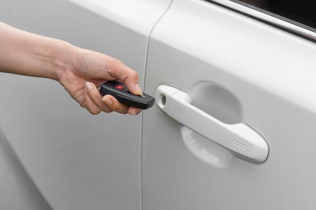 Hand met externe sleutel om auto te ontgrendelen