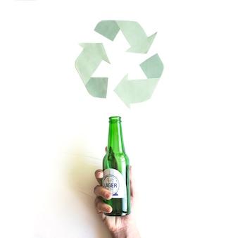 Hand met fles in de buurt van recycle symbool