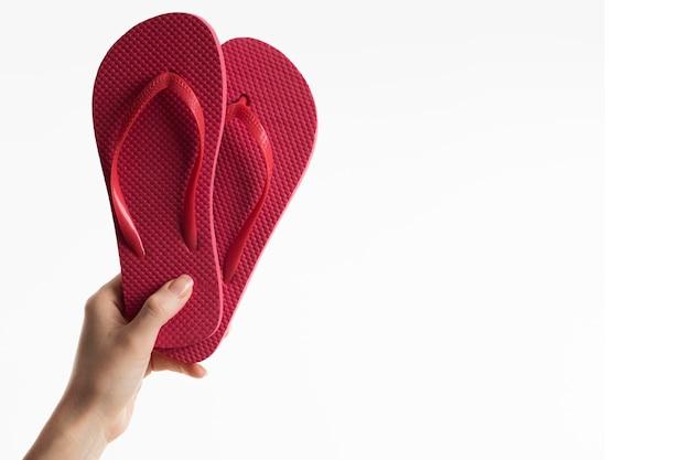 Hand met flip-flops met kopie ruimte