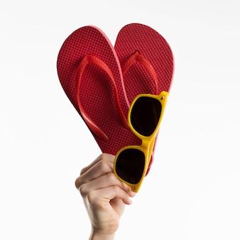 Hand met flip-flops met zonnebril
