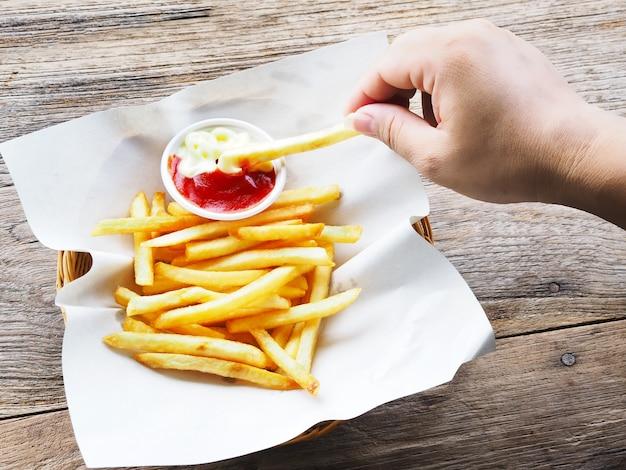 Hand met frietjes en dompelen tot ketchup