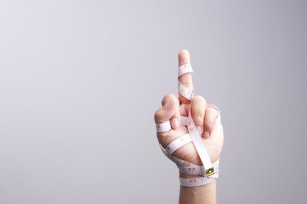 Hand met fuck je gebaar verpakt door meetlint