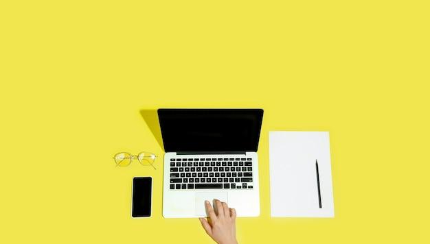 Hand met gadgets, apparaten op bovenaanzicht, leeg scherm met copyspace, minimalistische stijl. technologieën, modern, marketing. negatieve ruimte voor advertentie, flyer. gele kleur op de achtergrond. stijlvol, trendy.
