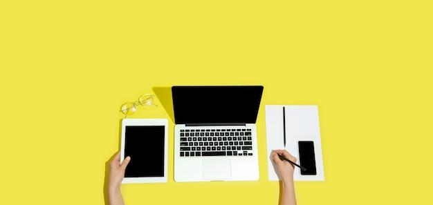 Hand met gadgets, apparaten op bovenaanzicht, leeg scherm met copyspace, minimalistische stijl