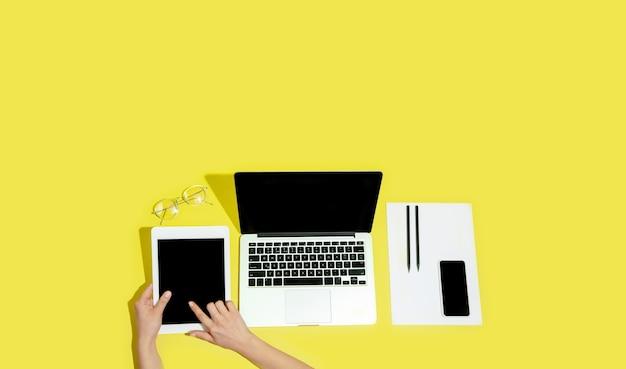 Hand met gadgets, apparaten op gele achtergrond bovenaanzicht, leeg scherm met copyspace, minimalistische stijl.