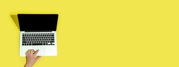 Hand met gadgets, laptop op gele achtergrond bovenaanzicht, leeg scherm met copyspace, minimalistische stijl.