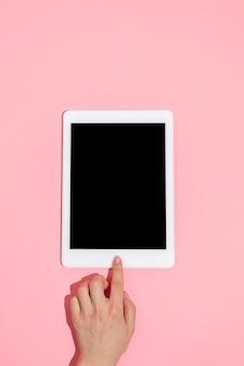 Hand met gadgets, tablet op bovenaanzicht, leeg scherm met copyspace, minimalistische stijl. technologieën, modern, marketing. negatieve ruimte voor reclame. koraal kleur op de achtergrond. stijlvol, trendy.
