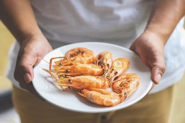Hand met garnalen gegrilde garnalen gekookt