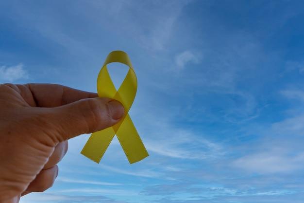 Hand met geel lint met blauwe hemelachtergrond gele september zelfmoordpreventiecampagne