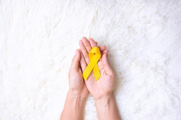 Hand met geel lint op witte achtergrond voor het ondersteunen van mensen die leven en ziekte. september suïcidepreventiedag, childhood cancer awareness-maand en wereldkankerdagconcept