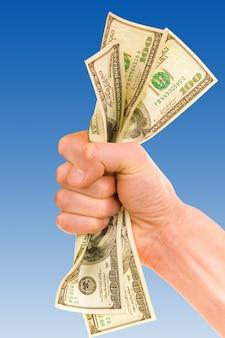 Hand met geld geïsoleerd op blauwe muur