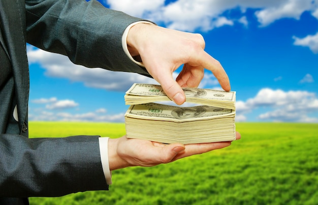 Hand met geld geïsoleerd op veld achtergrond