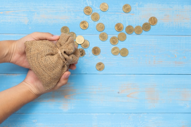 Hand met geld zak of tas met munten op blauwe houten achtergrond.