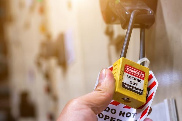 Hand met gele sleutelslot en tag voor elektrisch afgesneden proces