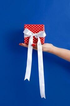 Hand met geschenkdoos op blauwe muur