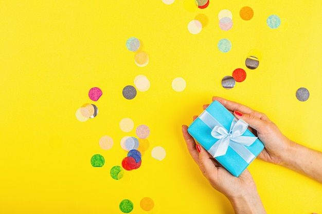 Hand met geschenkdoos op gele achtergrond