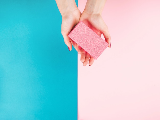 Hand met geschenkdoos op roze en turquoise