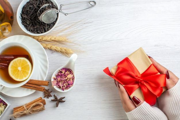 Hand met geschenken met rood lint en theepauze met kaneel