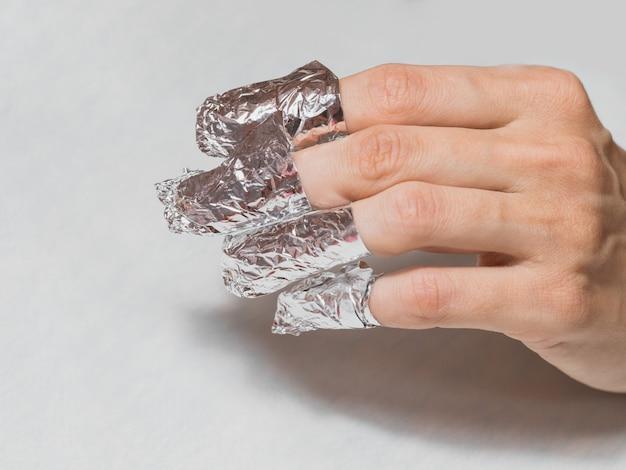 Hand met gewikkelde vingers in folie. manicure die vingernagels met folie verpakt tijdens de procedure van manicure bij een kuuroordsalon.