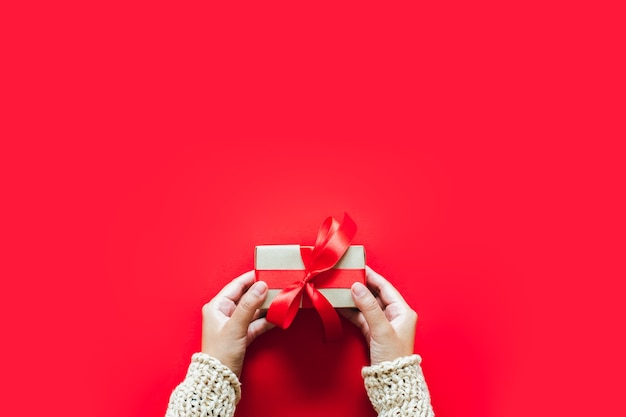 Hand met giftpresents doos over rode achtergrond voor kerst en gelukkig nieuwjaar concept.