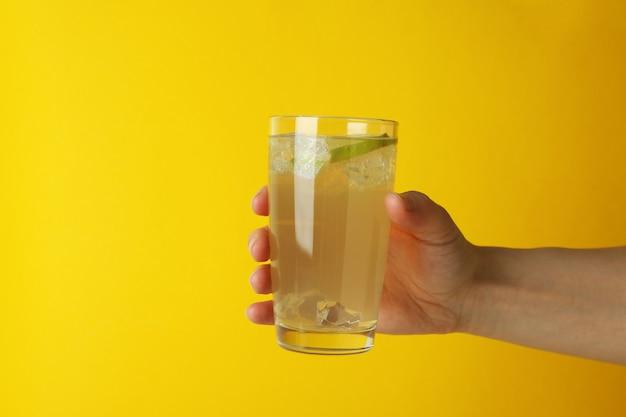 Hand met glas gemberbier op geel