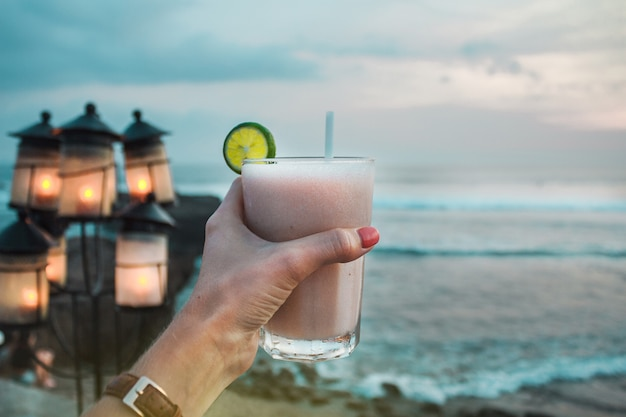 Hand met glas van de fruitcocktail op de achtergrond van oceaangolven stenen lantaarns en strand bali