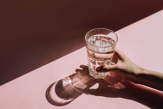 Hand met glas water tegen op tafel met direct zonlicht