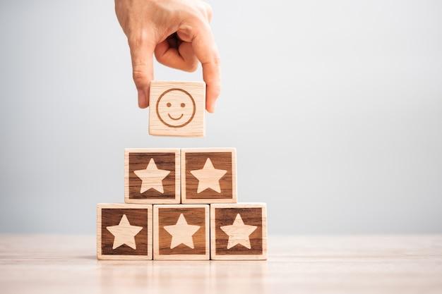 Hand met glimlach gezicht over ster symbool blokken op tabelachtergrond. servicebeoordeling, rangschikking, klantbeoordeling, tevredenheid, evaluatie en feedbackconcept