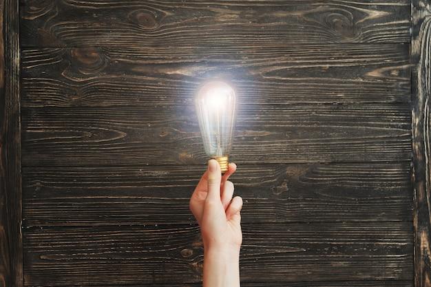 Hand met gloeilamp op een houten bord