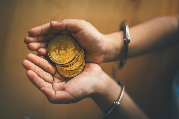 Hand met gouden bitcoin. criminele man met handboeien na een misdrijf gepleegd