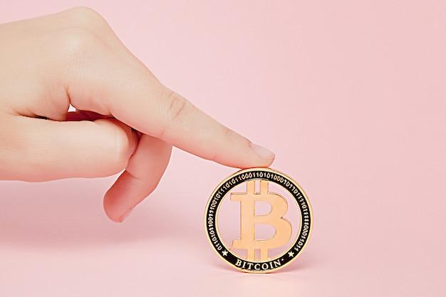 Hand met gouden bitcoin op roze