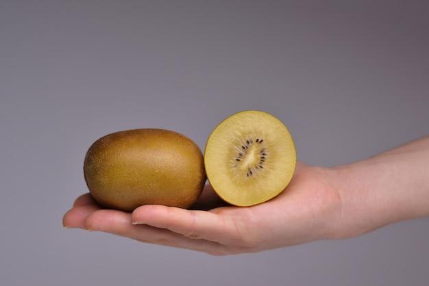 Hand met gouden kiwi geïsoleerd op een grijze achtergrond gele geïsoleerde kiwi's gouden kiwi's