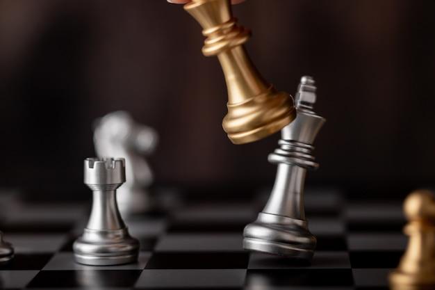 Hand met gouden koning aanval zilveren leider in het spel